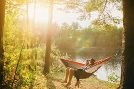 man and woman in hammock by water